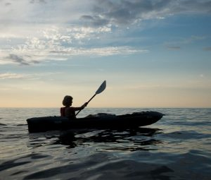 A person kayaking on the sea