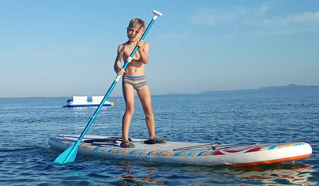A toddler on a standup paddleboard in Croatia