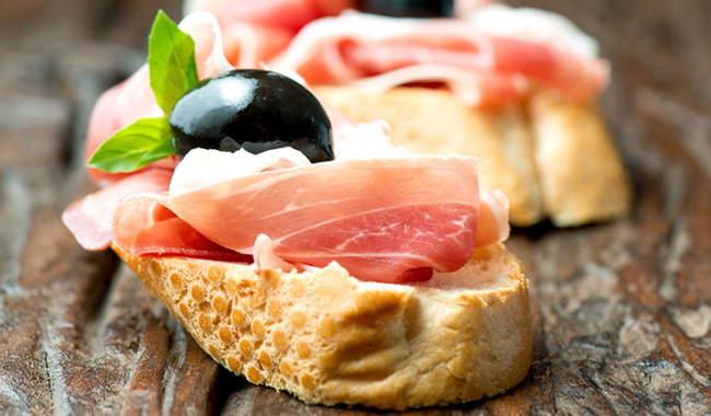 Proscuitto on a small piece of bread with a black olive as a garnish
