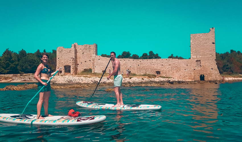 Two tourists standup paddleboarding around the Island of Vis in Croatia